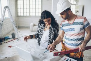 Young woman and construction worker looking at blueprints