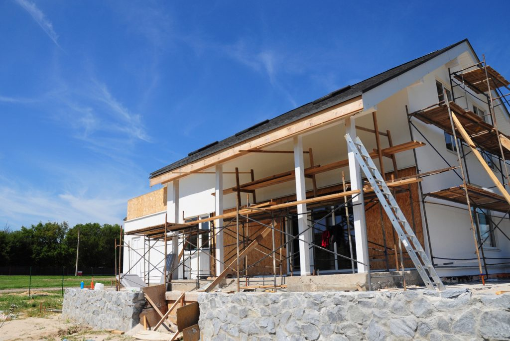 Renovate and repair residential house facade wall with mineral wool insulation, plastering, painting wall outdoors.