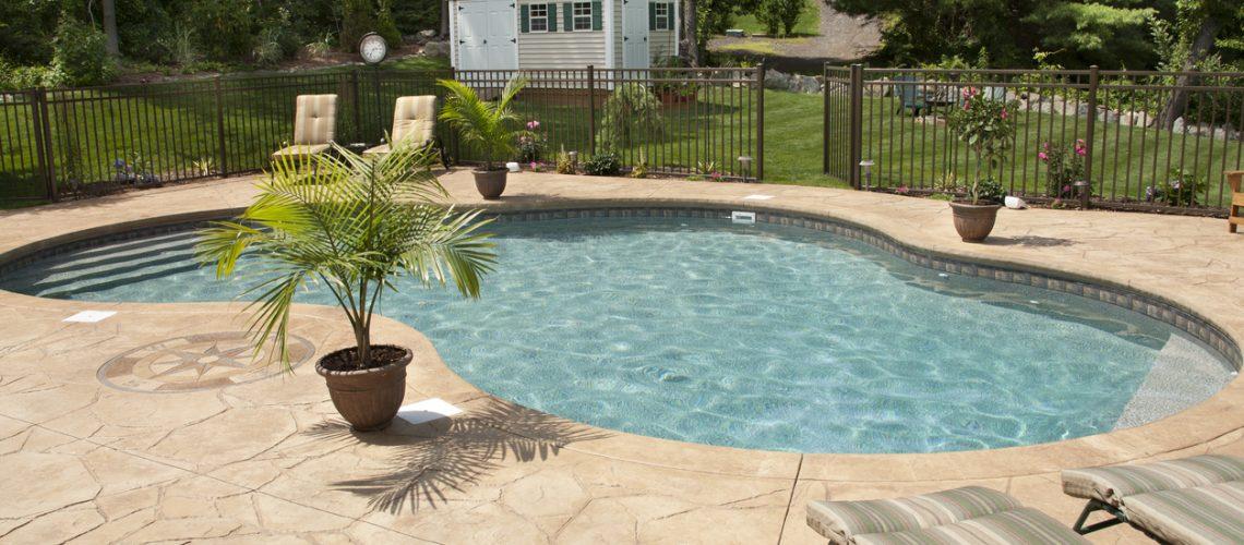 Lush backyard swimming pool and patio space.